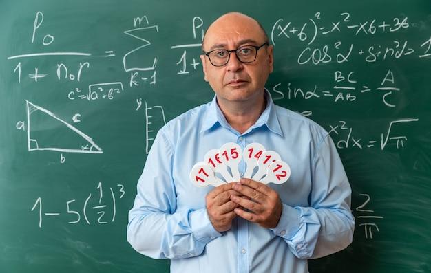 Fiducioso insegnante maschio di mezza età con gli occhiali in piedi davanti alla lavagna con in mano un numero di fan
