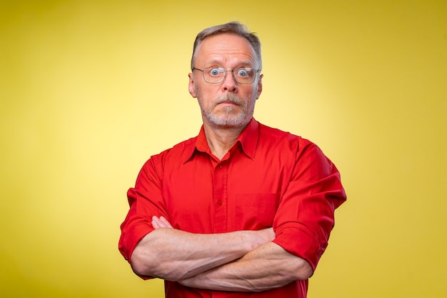 Confident middle aged man in red shirt with crossed hands over yellow background.