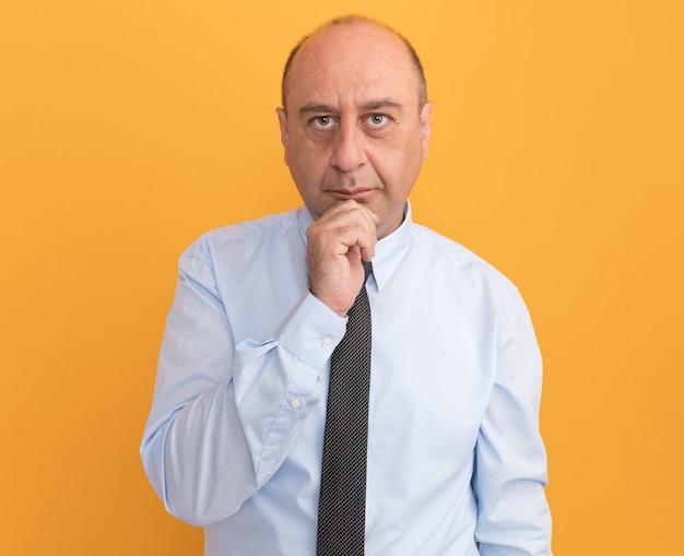 Fiducioso uomo di mezza età che indossa la maglietta bianca con cravatta ha afferrato il mento isolato sulla parete arancione