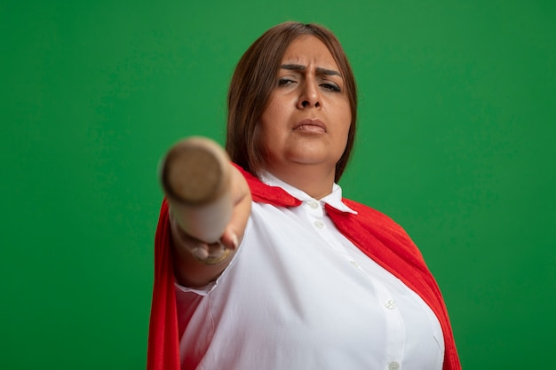 Confident middle-aged superhero female holding out baseball bat at camera isolated on green background