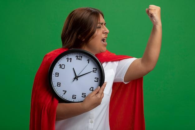 Orologio da parete femminile sicuro della tenuta del supereroe di mezza età che mostra forte gesto isolato sul verde