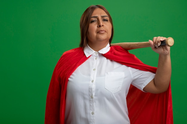 Confident middle-aged superhero female putting baseball bat on shoulder isolated on green background