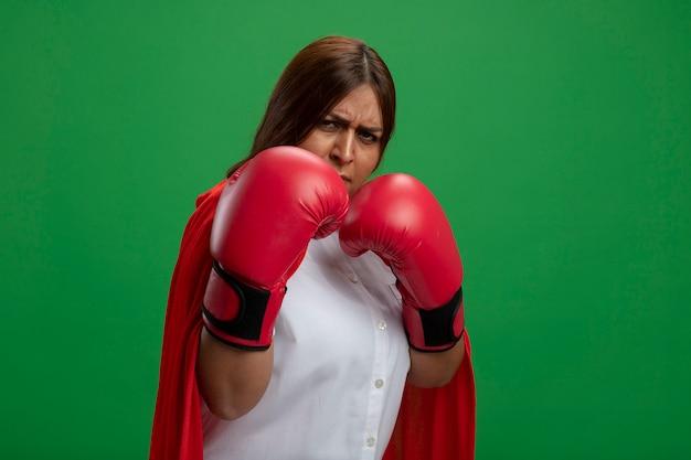 Guantoni da boxe da portare femminili sicuri del supereroe di mezza età che stanno nella posa di combattimento isolata sul verde