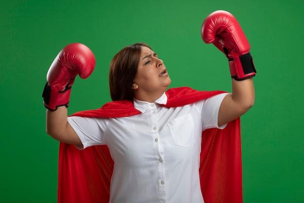 緑の背景に分離された戦闘ポーズで立っているボクシンググローブを身に着けている自信を持って中年のスーパーヒーローの女性