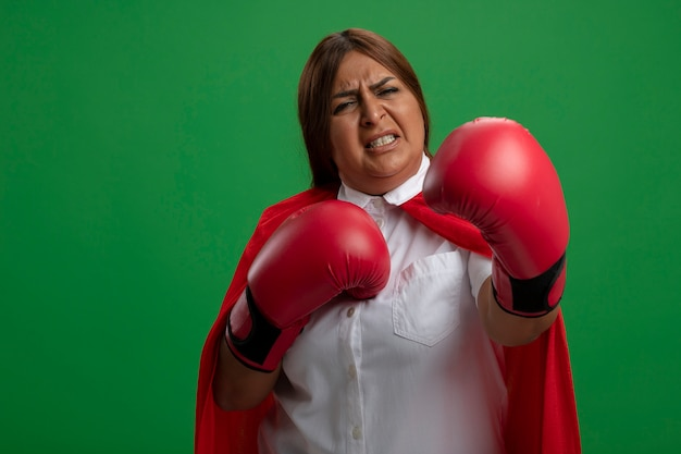 Уверенная женщина супергероя средних лет в боксерских перчатках, стоящая в боевой позе, изолированной на зеленом фоне