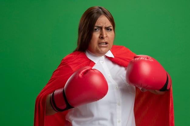 녹색에 고립 된 포즈 싸움에 서 권투 장갑을 끼고 자신감 중년 슈퍼 히어로 여성