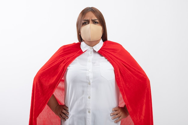 Femmina sicura del supereroe di mezza età che indossa la mascherina medica che mette le mani sull'anca isolata su bianco