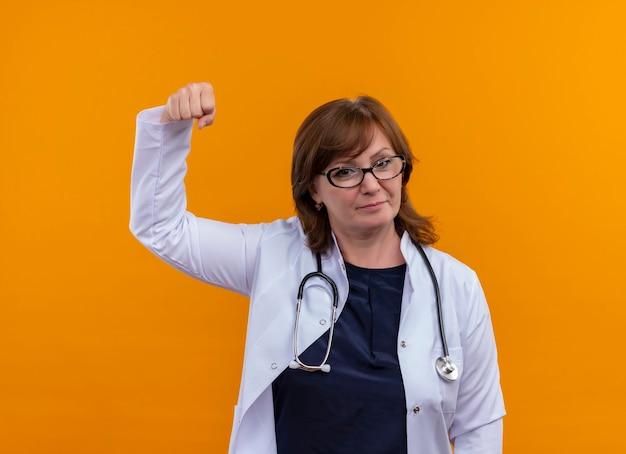眼鏡をかけて自信を持って中年女性医師、医療ローブ、孤立したオレンジ色の壁に拳を持ち上げる聴診器