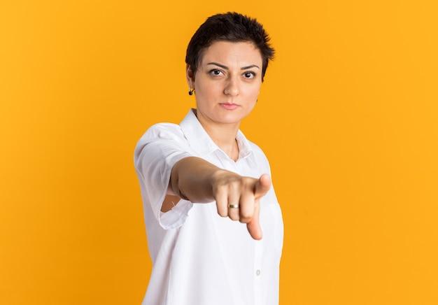 オレンジ色の壁に隔離された正面を見て、指している自信を持って中年女性