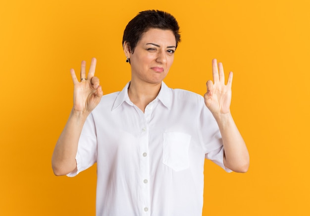 Confident middle-aged woman looking at camera winking doing ok sign