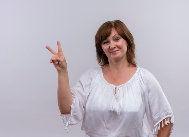 Confident middle-aged woman showing peace sign on isolated white wall