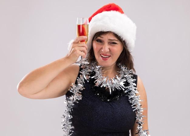 白い背景で隔離のカメラを見てシャンパンのガラスを上げる首の周りにサンタの帽子と見掛け倒しの花輪を身に着けている自信を持って中年女性