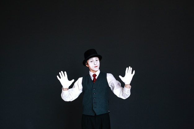 Confident mime holds his palms on invisible wall