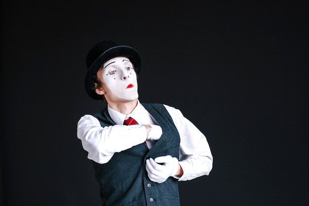Confident mime takes something from his pocket
