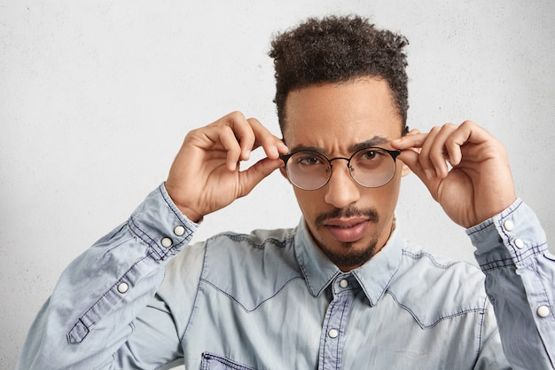Confident mixed race male enterpreneur keeps hands on frames of glasses, looks attentively
