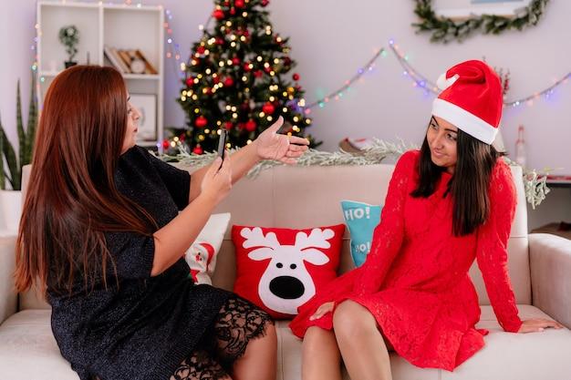 자신감이 어머니는 집에서 크리스마스 시간을 즐기고 소파에 앉아 전화에 그녀의 기쁘게 딸 사진을 걸립니다