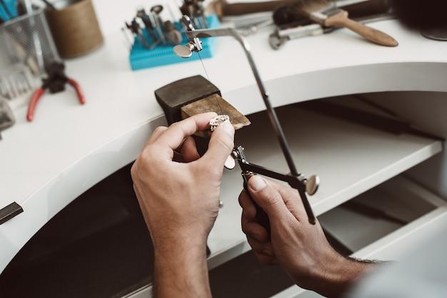 자신감 있는 모션입니다. 작업대에서 조정 가능한 전문 보석상의 톱 프레임으로 은반지를 만드는 보석상의 손 클로즈업 사진