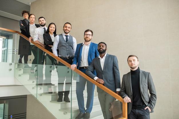 自信を持って多民族のビジネスチームのメンバーが階段に並んで立って見ている