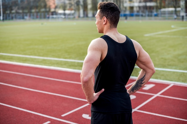 Confident muscular male athlete on red race track looking away