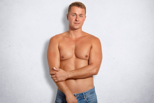 Confident muscular male being in good body shape, wears only jeans, goes in for sport regularly, isolated on white concrete wall, keeps hands partly crossed. people, healthy lifestyle concept
