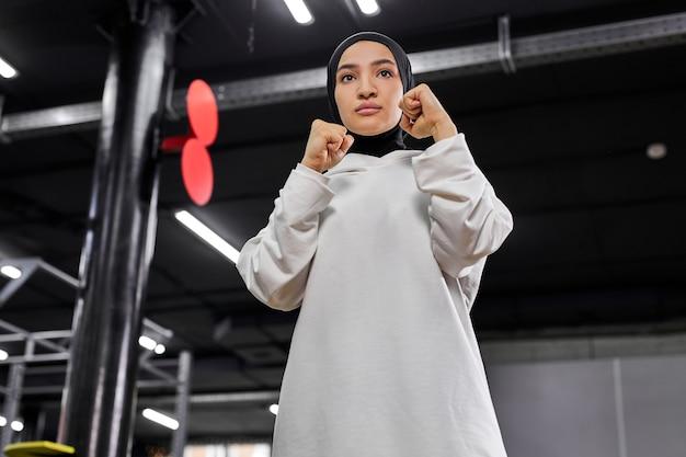 戦闘機のポーズで立って、打つつもりで、フィットネスセンターでボクシングに従事し、白いヒジャーブを身に着けている自信のあるイスラム教徒のスポーツウーマン。スポーツ、トレーニング、フィットネスのコンセプト