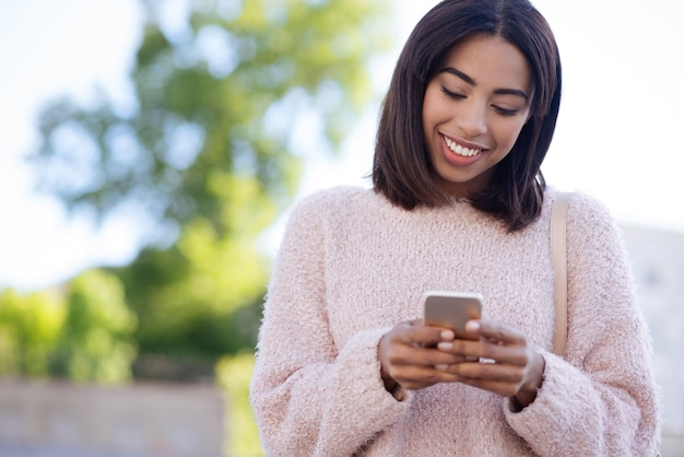 Confident nice energetic girl using her smartphone for communicating with her friends and replying them within seconds