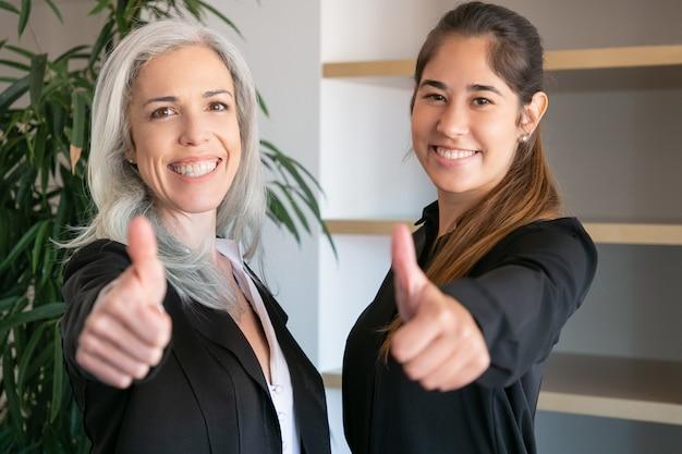 親指を立てて笑っている自信のあるオフィスの雇用者。 2人の幸せなプロのビジネスウーマンが一緒に立って、会議室でポーズします。チームワーク、ビジネス、協力の概念