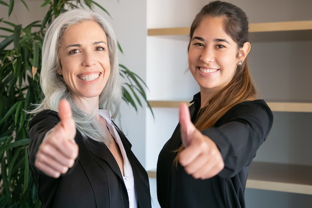 Confident office employers thumbing up and smiling. two happy professional businesswomen standing together and posing at meeting room. teamwork, business and cooperation concept
