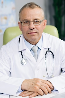 Confident old mature male head doctor physician in white medical uniform in glasses sitting at workplace