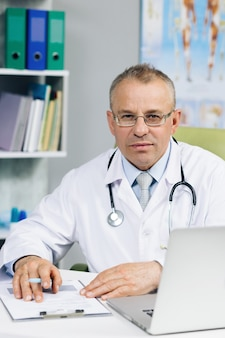 Confident old mature male head doctor physician in white medical uniform in glasses sitting at workplace.