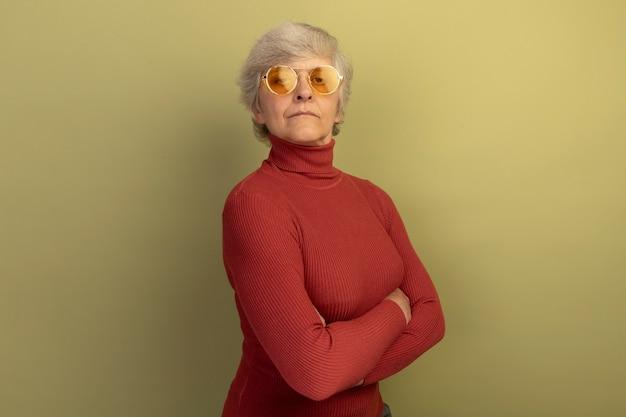 Fiduciosa vecchia donna che indossa un maglione a collo alto rosso e occhiali da sole in piedi con la postura chiusa in vista di profilo isolata sulla parete verde oliva con spazio copia