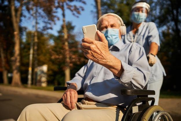 야외에서 시간을 보내는 동안 헤드폰을 끼고 무언가를 듣고 있는 자신감 있는 나이든 남성
