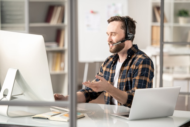 Confident operator explaining further details or answering question of client while sitting in front of computer screen