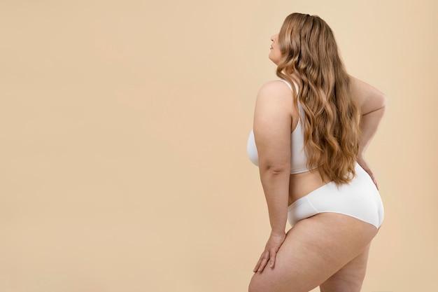 Уверенная негабаритная женщина позирует в нижнем белье