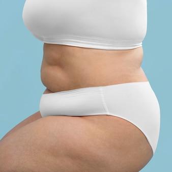 Fiduciosa donna oversize in posa in lingerie bianca