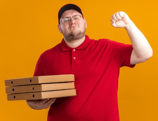 광학 안경에 자신감과 체중 젊은 배달원 피자 상자를 들고 복사 공간이 오렌지 벽에 고립 주먹을 유지