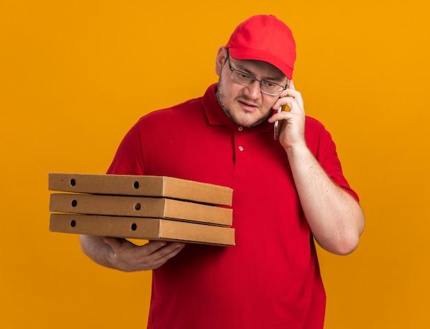 광학 안경에 자신감과 체중 젊은 배달원 피자 상자를 들고 복사 공간이 오렌지 벽에 고립 된 전화 통화