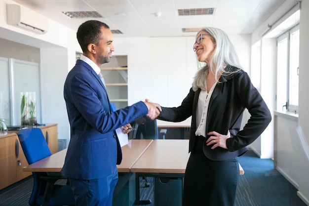 Confident partners handshaking or greeting in meeting room. successful content businessman and professional grey-haired manager concluding contract. teamwork, business and partnership concept