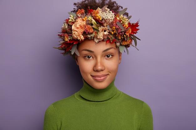 自信を持って平和な暗い肌の女性モデルは、カメラを直接見て、穏やかな幸せな表情を持ち、素敵な手作りの花輪を身に着け、紫色の背景に対して屋内に立っています。