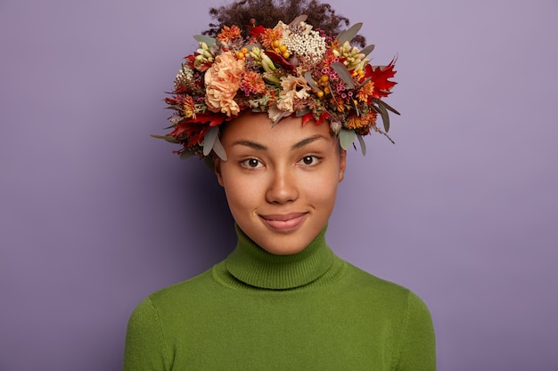 Confident peaceful dark skinned female model looks directly at camera, has calm happy expression, wears nice handmade wreath, stands indoor against purple background.