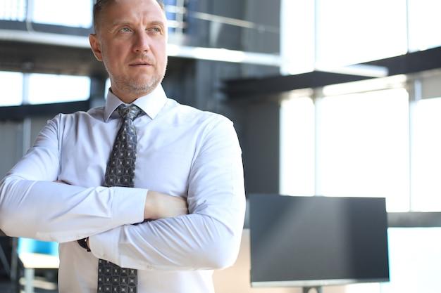 Confident pensive mature business man in modern office.
