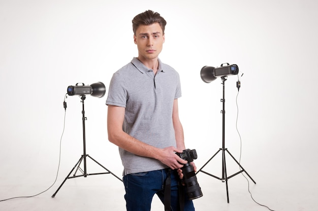 Confident photographer. handsome young man in polo shirt leaning at the tripod with camera while standing in studio with lighting equipment on background