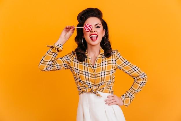 분홍색 막대 사탕과 함께 포즈 자신감 핀업 소녀입니다. 노란색 배경에 고립 된 체크 무늬 셔츠에 세련 된 갈색 머리 여자의 스튜디오 샷.