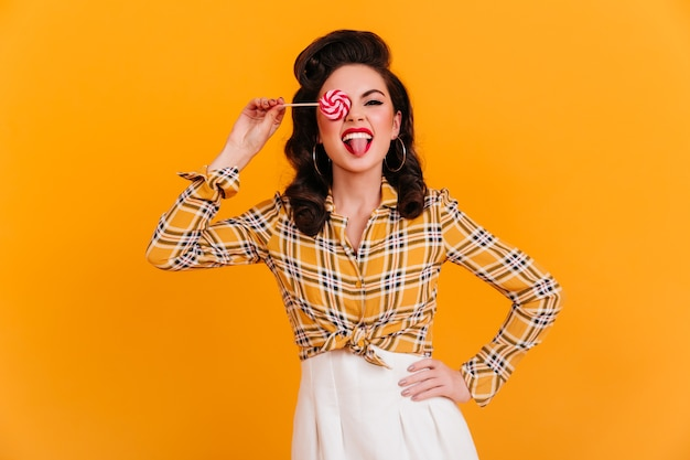 Confident pinup girl posing with pink lollipop. studio shot of stylish brunette woman in checkered shirt isolated on yellow background.