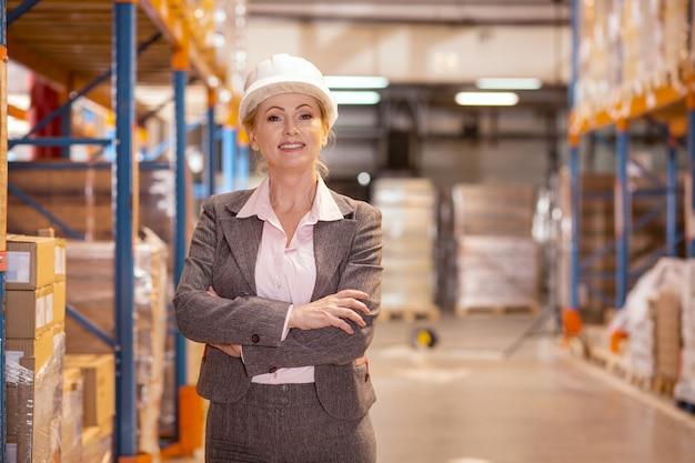 창고에서 작업하는 동안 당신을 찾고 자신감 즐거운 여자.
