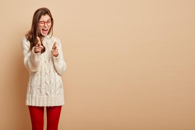 자신감이 넘치는 여성은 눈을 깜박이고, 자신감있는 표정을 지으며, 두 손가락으로 포인트를주고, 안경을 쓰고, 베이지 색 벽 위에 서고, 발표 나 텍스트를위한 공간을 복사합니다.