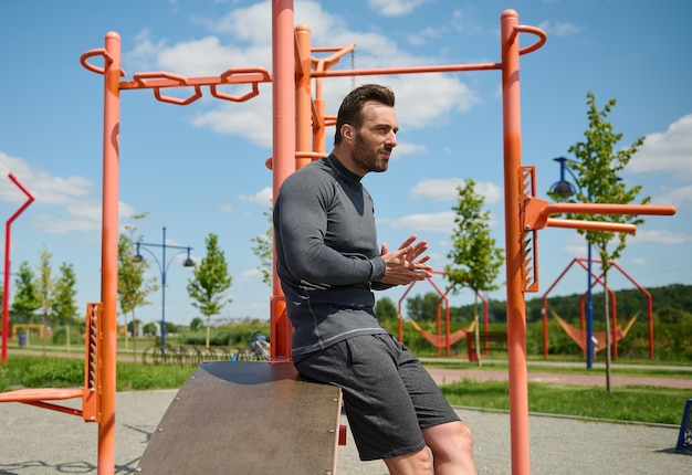 Confident portrait of attractive sporty man, handsome macho, european caucasian muscular build athlete in sports wear on the background of cross bars and gym machines in summer outdoor sportsground