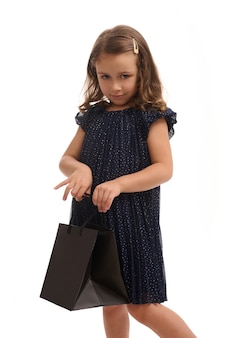 Confident portrait isolated on white background with copy space of pretty little girl looking at camera with black shopping packet in her hands,dressed in evening dark blue dress. black friday concept