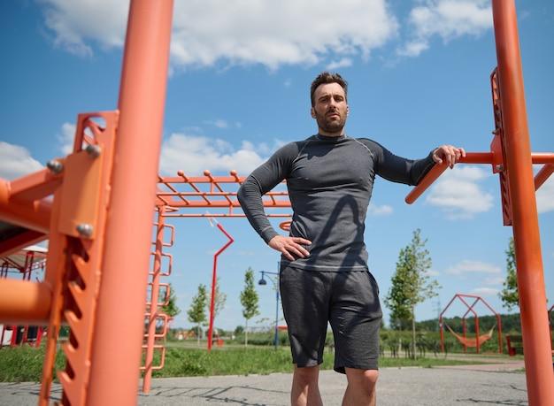 カメラを見て、腰に腕を持ってスポーツフィールドに立っているハンサムなヨーロッパのスポーツマンアスリートの自信を持って肖像画。トレーニング後に休んでいるスポーツウェアのハンサムな白人男性