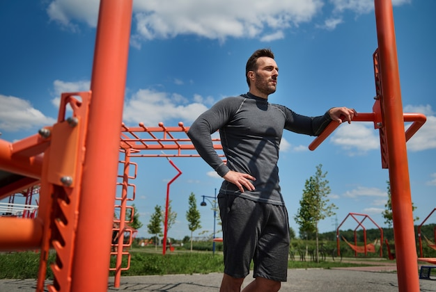 腰に腕を持ってスポーツフィールドに立って、目をそらしているハンサムなヨーロッパのスポーツマンアスリートの自信を持って肖像画。トレーニング後に休んでいるスポーツウェアのハンサムな白人男性